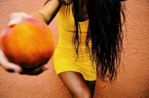 Girl in yellow mini dress holding peach